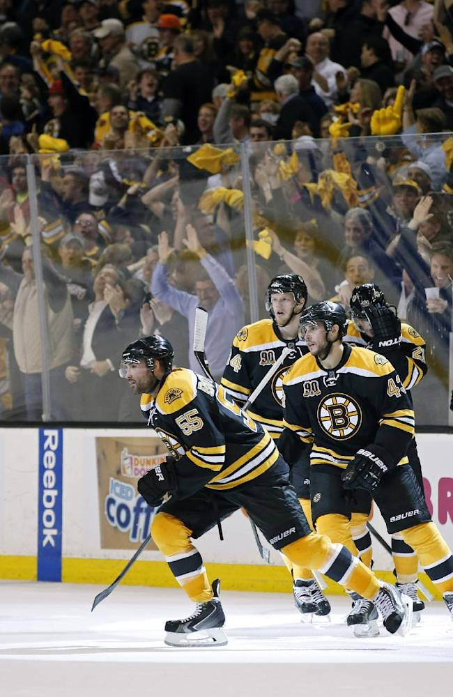 Fans and Boston Bruins players celebrate after Johnny Boychuk's (55) goal against the Montreal Canadiens during the third period in Game 1 of an NHL hockey second-round playoff series in Boston, Thursday, May 1, 2014