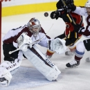 Colorado Avalanche goalie Semyon Varlamov, left, from Russia, looks at the puck as Colorado's Tyson Barrie, right, battles with Calgary Flames' Johnny Gaudreau during first-period NHL hockey game action in Calgary, Alberta, Thursday, Dec. 4, 2014 The Asso