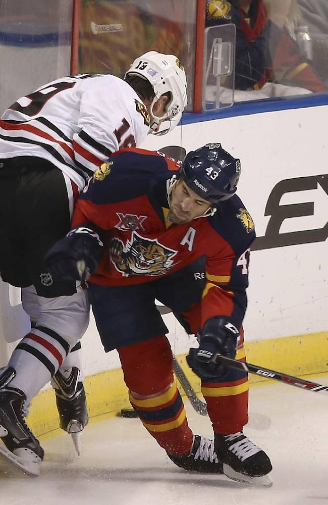 Florida Panthers' Mike Weaver (43) tries to block Chicago Blackhawks' Jonathan Toews (19) from chasing the puck during the first period of an NHL hockey game in Sunrise, Fla., Tuesday, Oct. 22, 2013