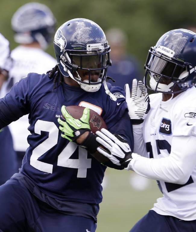 Seattle Seahawks' Marshawn Lynch (24) runs as Jeron Johnson comes in on defense during an NFL football minicamp on Wednesday, June 12, 2013, in Renton, Wash