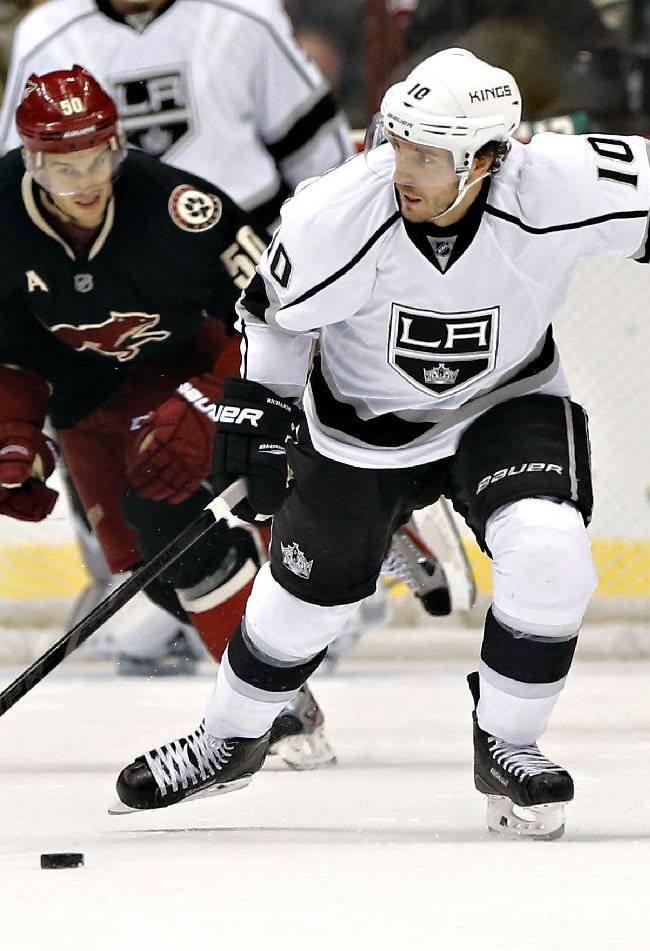 Los Angeles Kings' Mike Richards, right, pushes the puck up the ice as Phoenix Coyotes' Antoine Vermette pursues during the first period of an NHL hockey game, Tuesday, Oct. 29, 2013, in Glendale, Ariz