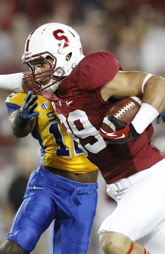 In this Sept. 7, 2013, file photo, Stanford wide receiver Devon Cajuste (89) breaks a tackle against San Jose State cornerback Forrest Hightower (12) for a touchdown during the first half of an NCAA football game in Stanford, Calif. Cajuste is developing into one of the team's top targets after selecting Stanford over eight other schools, including Harvard,because every other program wanted to turn him into a tight end