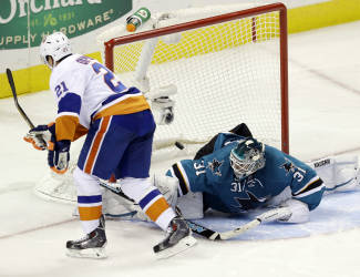 New York Islanders' Kyle Okposo (21) scores the game-winning goal past San Jose Sharks goalie Antti Niemi, of Finland, during the shootout of an NHL hockey game on Tuesday, Dec. 10, 2013, in San Jose, Calif. New York won 3-2. (AP Photo/Marcio Jose Sanchez)