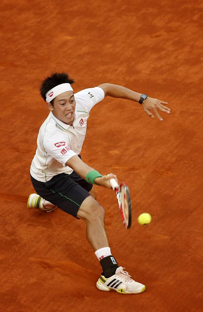 Kei Nishikori from Japan returns the ball during a Madrid Open tennis tournament match against David Ferrer in Madrid, Spain, Saturday, May 10, 2014