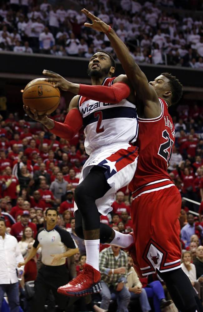 Washington Wizards guard John Wall (2) shoots past Chicago Bulls guard Jimmy Butler (21) in the second half of Game 3 of an opening-round NBA basketball playoff series on Friday, April 25, 2014, in Washington. The Bulls won 100-97