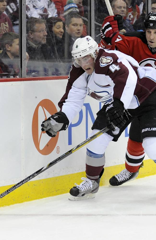 Colorado Avalanche's Tyson Barrie controls the puck as he is checked by New Jersey Devils' Ryan Clowe, right, during the second period of an NHL hockey game Monday, Feb. 3, 2014, in Newark, N.J
