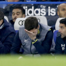 Tottenham Hotspur's head coach Mauricio Pochettino, center, holds his hand to his face, as his club captain Younes Kaboul, top right, who was an unused substitute watches near the end of the English Premier League soccer match between Chelsea and Tottenha