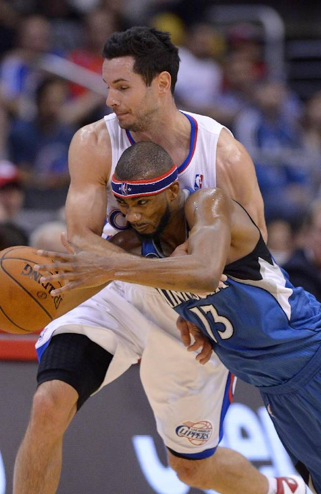 Los Angeles Clippers guard J.J. Redick, top, and Minnesota Timberwolves forward Corey Brewer go after a loose ball during the second half of an NBA basketball game, Monday, Nov. 11, 2013, in Los Angeles. The Clippers won 109-107