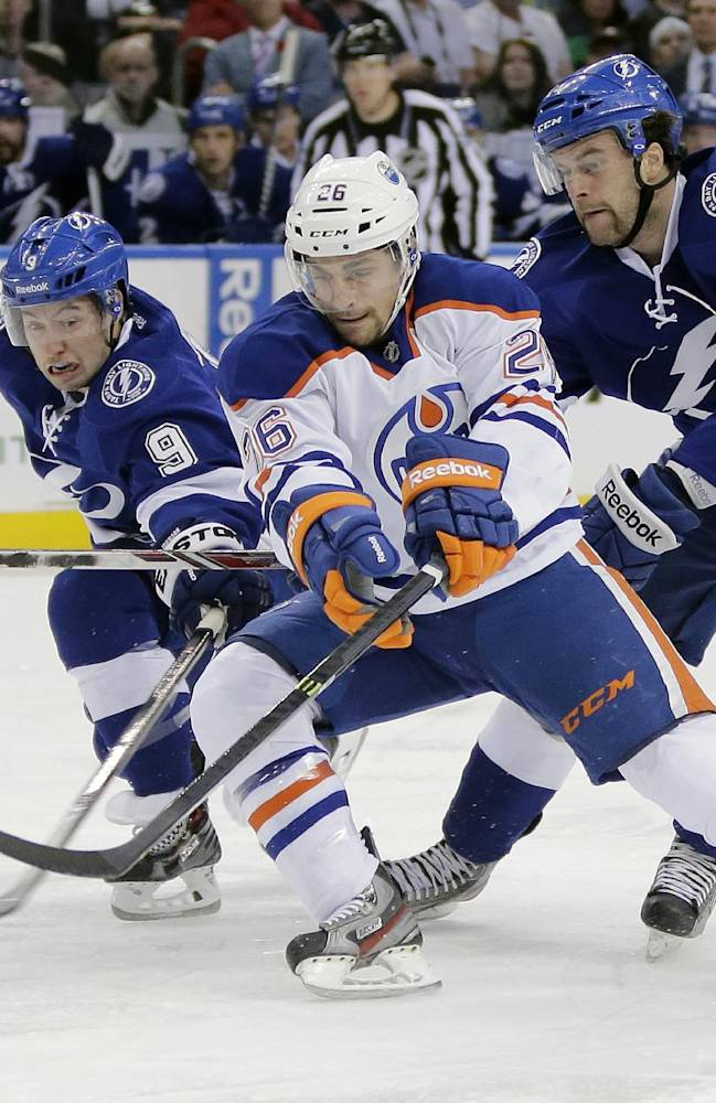 Edmonton Oilers center Mark Arcobello (26) slips between Tampa Bay Lightning center Tyler Johnson (9) and right winger Brett Connolly during the first period of an NHL hockey game on Thursday, Nov. 7, 2013, in Tampa, Fla