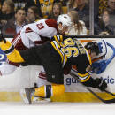 Phoenix Coyotes left wing Lauri Korpikoski (28) knocks down Boston Bruins defenseman Kevan Miller during the first period of an NHL hockey game in Boston Thursday, March 13, 2014. (AP Photo/Winslow Townson)
