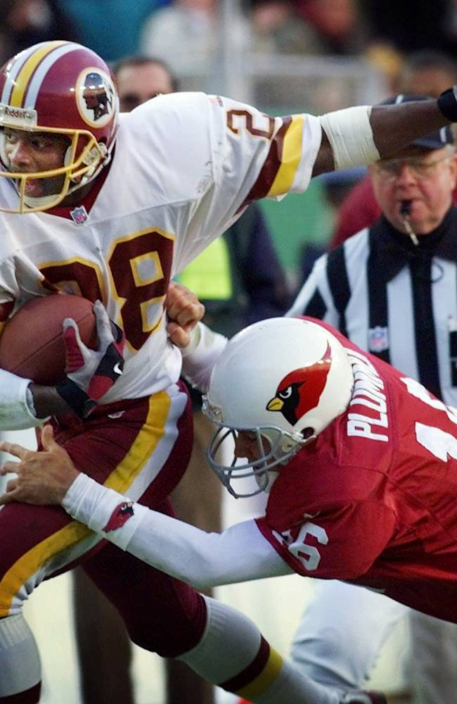 In this Dec. 12, 1999, file photo, Arizona Cardinals quarterback Jake Plummer (16) tries to tackle Washington Redskins cornerback Darrell Green (28) who intercepted Plummer's pass during the fourth quarter of an NFL football game at FedEx Field in Landover, Md.  The former Washington Redskins cornerback, elected to the Pro Football Hall of Fame in 2008, looks around today's NFL and sees a lack of talent at his old job.
