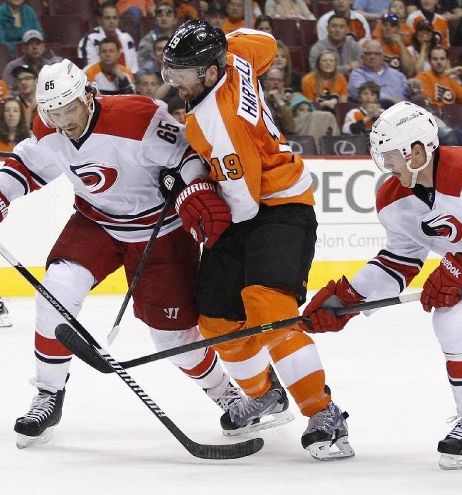 Philadelphia Flyers' Scott Hartnell, center, goes after the puck as Carolina Hurricanes' Ron Hainsey, left, and Riley Nash, right, try to keep him away from it during the second period of an NHL hockey game, Sunday, April 13, 2014, in Philadelphia