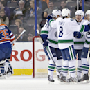 Vancouver Canucks' Alexander Edler (23), Chris Tanev (8), Alex Burrows (14) and Nick Bonino (13) celebrate a goal as Edmonton Oilers goalie Viktor Fasth (35) skates away during the second period of a preseason NHL hockey hockey game Thursday, Oct. 2, 2014