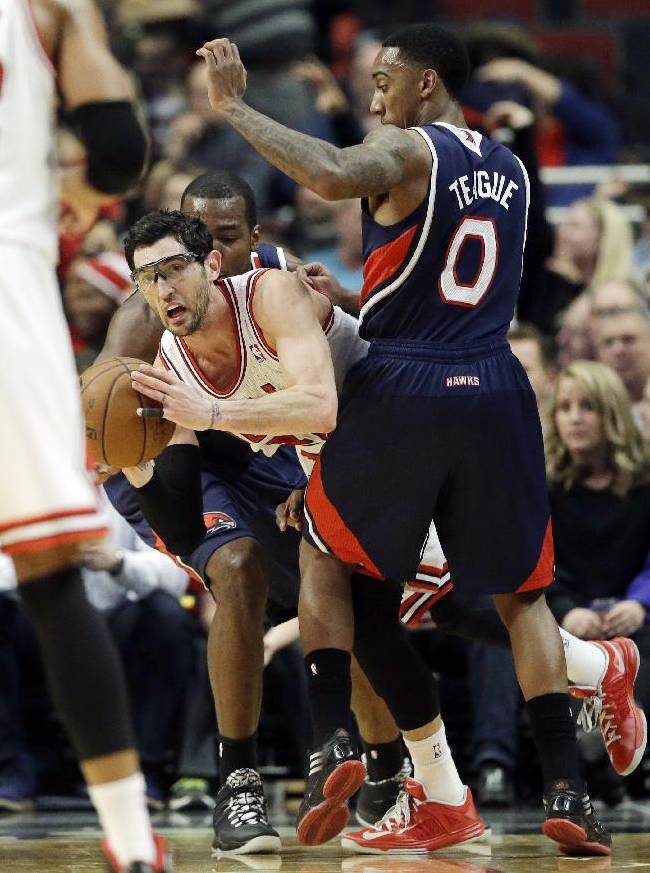 Chicago Bulls guard Kirk Hinrich, center, looks to pass as Atlanta Hawks forward Paul Millsap, left, and guard Jeff Teague guard during the first half of an NBA basketball game in Chicago on Saturday, Jan. 4, 2014
