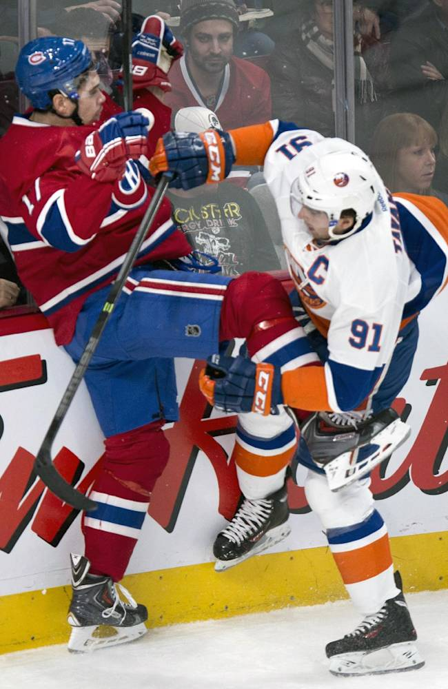 Montreal Canadiens' Rene Bourque takes a hit from New York Islanders' John Tavares during first period of an NHL hockey game on Sunday, Nov. 10, 2013, in Montreal