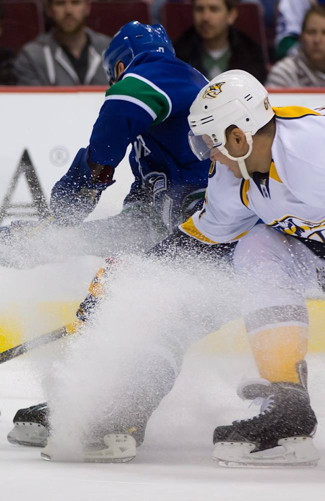 Nashville Predators' Victor Bartley, right, catches up to defend against Vancouver Canucks' Zack Kassian on a breakaway during first-period NHL hockey game action in Vancouver, British Columbia, Wednesday, March 19, 2014