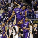 James Madison guard Andre Nation (15) celebrates with teammates Devon Moore (40) and Ron Curry (2) during the first half of the Colonial Athletic Conference tournament championship NCAA college basketball game in Richmond, Va., Monday, March 11, 2013. James Madison won 70-57. (AP Photo/Steve Helber)