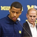 Michigan sophomore guard Trey Burke, with Michigan coach John Beilein standing by, announces he will enter the NBA draft at a news conference, Sunday, April 14, 2013, at Crisler Center in Ann Arbor, Mich. He led Michigan to the NCAA title game, where the Wolverines lost to Louisville. (AP Photo/Tony Ding)