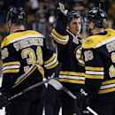 Boston Bruins center Patrice Bergeron, second from right, celebrates with teammates right wing Reilly Smith (18) and center Carl Soderberg (34) after their 7-2 victory over the Ottawa Senators in an NHL hockey game in Boston, Saturday, Feb. 8, 2014 The As
