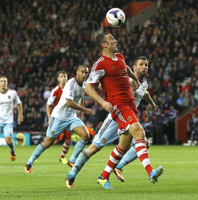 Southampton's Rickie Lambert heads the ball as West Ham's Razvan Rat, right, follows during the English Premier League soccer match between Southampton and West Ham United at St Mary's Stadium in Southampton, England Sunday, Sept. 15, 2013