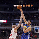 Golden State Warriors center Andrew Bogut (12) passes the ball over Chicago Bulls forward Carlos Boozer (5) during the first half of an NBA basketball game, Wednesday, Feb. 26, 2014, in Chicago The Associated Press