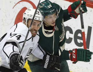 Los Angeles Kings' Dwight King, left, and Minnesota Wild's Erik Haula, of Finland, race behind the net for the puck in the first period of an NHL hockey game, Saturday, March 28, 2015, in St. Paul, Minn. (AP Photo/Jim Mone)