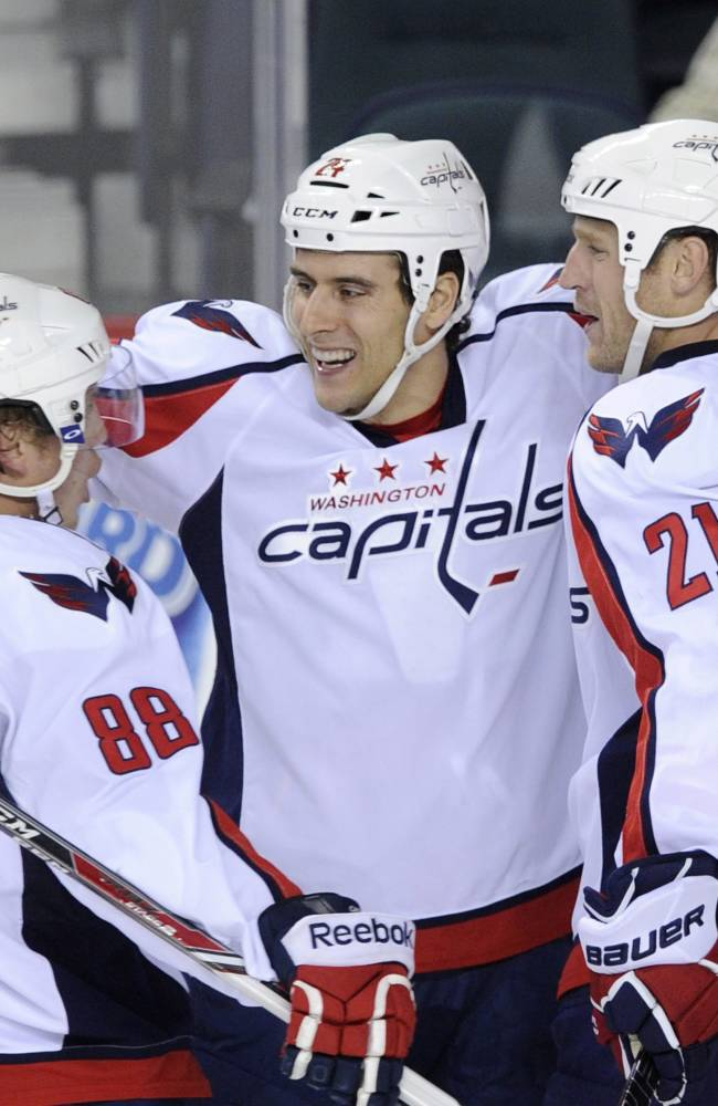 Washington Capitals' Aaron Volpatti, centre, celebrates his goal against the Calgary Flames with teammates Nate Schmidt, left, and Brooks Laich during second period NHL action in Calgary, Alta., Saturday, Oct. 26, 2013
