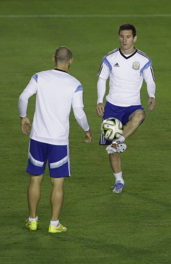 Argentina's Lionel Messi, right, controls the ball next to Javier Mascherano at the Vasco da Gama stadium during an official training session the day before the World Cup final soccer match between Germany and Argentina in Rio de Janeiro, Brazil, Saturday, July 12, 2014