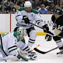 Dallas Stars goalie Kari Lehtonen (32) dives to cover a loose puck before Pittsburgh Penguins' Chris Kunitz (14) can get his stick on it during the second period of an NHL hockey game in Pittsburgh, Tuesday, March 18, 2014 The Associated Press
