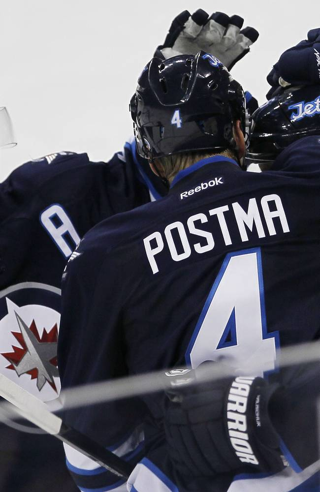 Winnipeg Jets' Tobias Enstrom (39), Paul Postma (4) and Matt Halishchuk (15) celebrate Halishchuk's goal against the Ottawa Senators during the second period of a preseason NHL hockey game in Winnipeg on Sunday, Sept. 15, 2013
