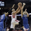 Houston Rockets guard Jeremy Lin (7) drives to the basket between Orlando Magic forward Tobias Harris (12) and center Nikola Vucevic (9) during the second half of an NBA basketball game Monday, April 1, 2013 in Houston. Houston won 110-103. (AP Photo/Bob Levey)