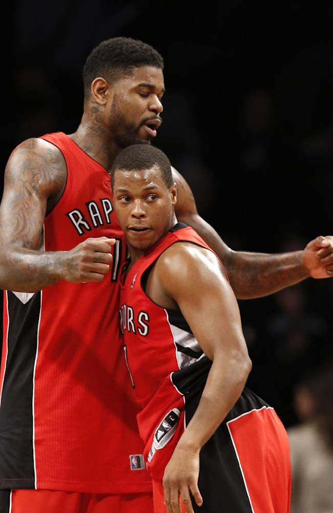 Toronto Raptors forward Amir Johnson (15) and guard Kyle Lowry (7) celebrate after the Raptors defeated the Brooklyn Nets 87-79 in Game 4 of an NBA basketball first-round playoff series at the Barclays Center, Sunday, April 27, 2014, in New York. The Raptors evened the series at 2-2
