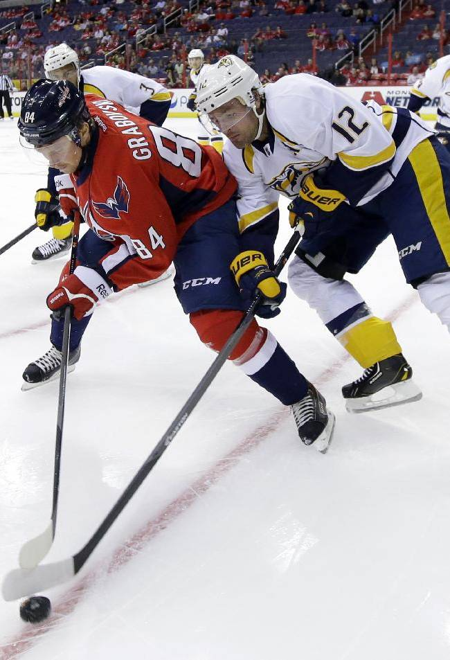Washington Capitals center Mikhail Grabovski (84), from Germany, battles for the puck with Nashville Predators center Mike Fisher (12) during the first period of a preseason NHL hockey game on Wednesday, Sept. 25, 2013, in Washington. The Capitals won 4-1