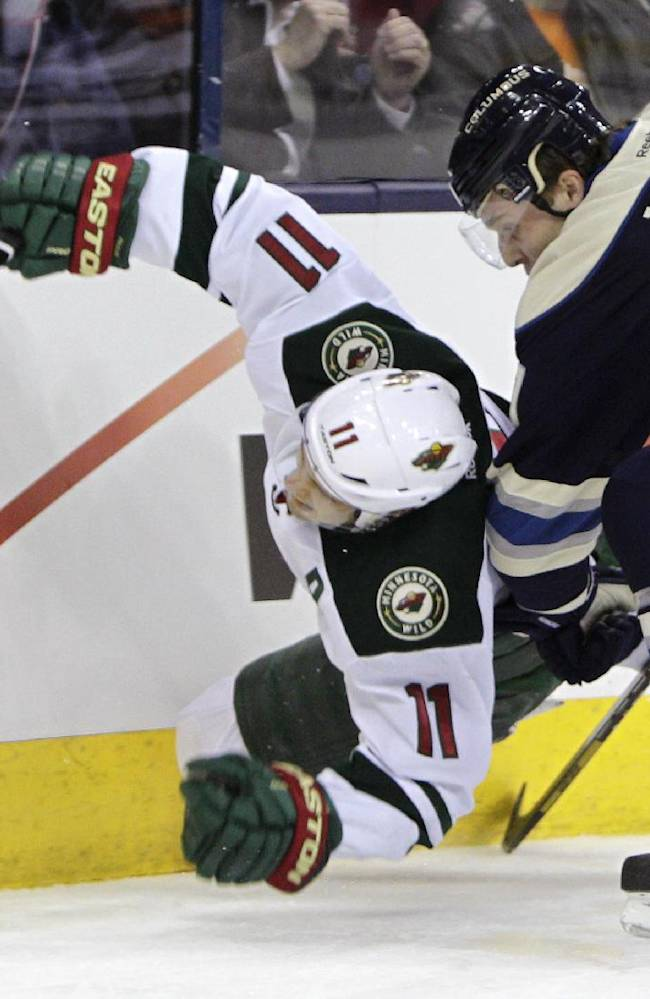 Columbus Blue Jackets' Jack Johnson, right, checks Minnesota Wild's Zach Parise during the first period of an NHL hockey game on Friday, Dec. 6, 2013, in Columbus, Ohio