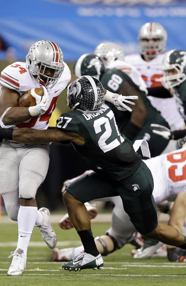 In this Dec. 7, 2013 file photo, Ohio State's Carlos Hyde (34) is tackled by Michigan State's Kurtis Drummond (27) during the second half of a Big Ten Conference championship NCAA college football game in Indianapolis. Even though it has sunshine, warm weather and spectacular food and nightlife, the Orange Bowl wasn't exactly where Ohio State wanted to play, it's a pretty good consolation prize after they suffered their first loss in two seasons in the Big Ten title game