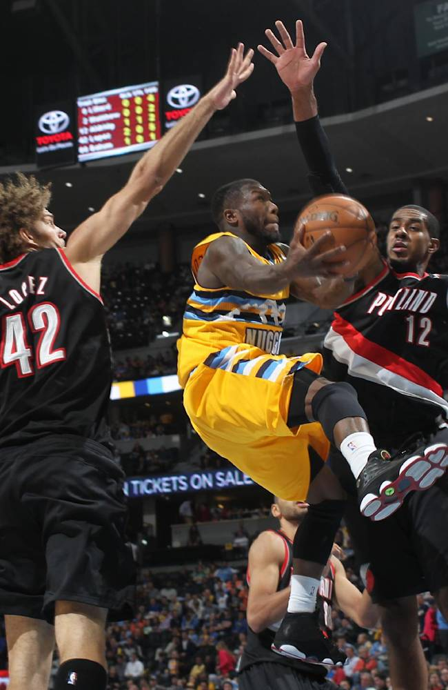 Denver Nuggets guard Nate Robinson, center, slips in for a shot between Portland Trail Blazers center Robin Lopez, left, and forward LaMarcus Aldridge in the fourth quarter of Portland's 113-98 victory in an NBA basketball game in Denver, Friday, Nov. 1, 2013