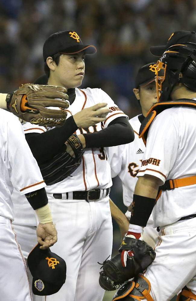 Yomiuri Giants closer Kentaro Nishimura, second from left, confers with catcher Shinnosuke Abe, right, on the mound after hitting Rakuten Eagles' Kazuya Fujita with a pitch in the 10th inning of Game 5 of baseball's Japan Series at Tokyo Dome in Tokyo, Thursday, Oct. 31, 2013. At left is third baseman Shuichi Murata (25)