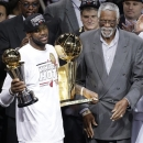 The Miami Heat's LeBron James, left, holding the Larry O'Brien NBA Championship Trophy and his Bill Russell NBA Finals Most Valuable Player Award after Game 7 of the NBA basketball championship game against the San Antonio Spurs, Friday, June 21, 2013, in Miami. The Miami Heat defeated the San Antonio Spurs 95-88 to win their second straight NBA championship. Former NBA player Bill Russell looks on. (AP Photo/Wilfredo Lee)