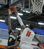 Marquette guard JaJuan Johnson (5) gets his shot blocked by Cal State Fullerton guard Jared Gentry (11) in the second half of an NCAA college basketball game at the Wooden Legacy tournament Thursday, Nov. 28, 2013, in Fullerton, Calif. Marquette won 86-66. (AP Photo/Alex Gallardo)