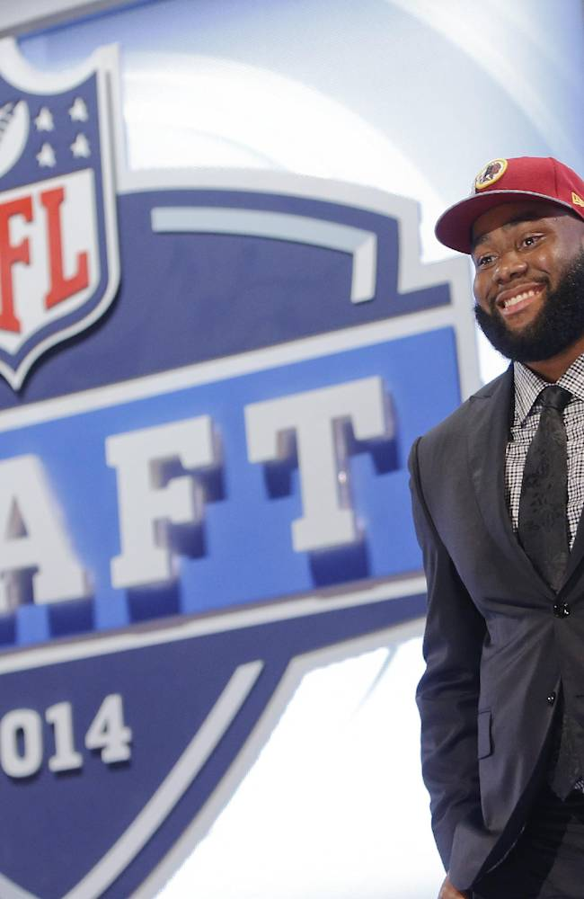 In this May 9, 2014, file photo, Virginia tackle Morgan Moses poses for photos after being selected in the third round, 66th overall by the Washington Redskins in the NFL draft in New York. After rookie camp, he plans to skedaddle to Charlottesville so he could march in his graduation ceremony Sunday at the University of Virginia, with a degree in anthropology, no less