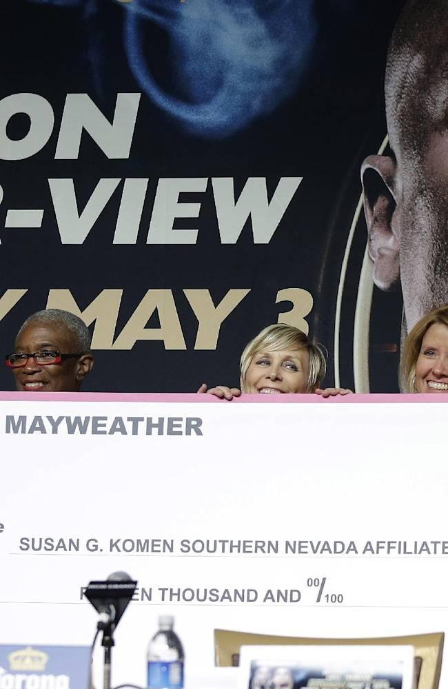 Boxer Floyd Mayweather Jr., left, presents a check for $15,000 to Susan G. Komen for the Cure during a news conference Wednesday, April 30, 2014, in Las Vegas. Mayweather will square off in a welterweight title fight against Marcos Maidana on Saturday, May 3. Komen, is the most widely known, largest and best-funded breast cancer organization in the United States