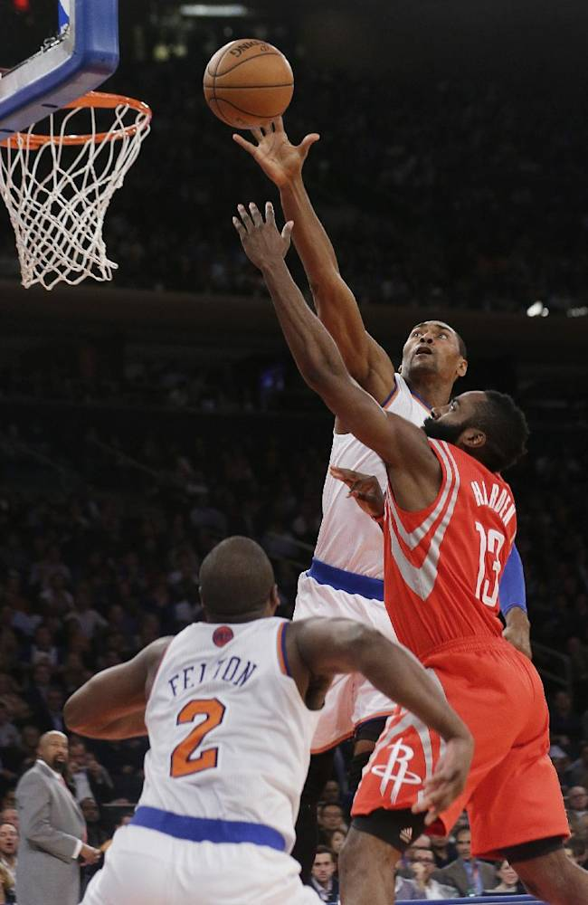New York Knicks' Metta World Peace blocks a shot by Houston Rockets' James Harden, right, as Knicks' Raymond Felton, left, defends during the second half of an NBA basketball game Thursday, Nov. 14, 2013, in New York. The Rockets won 109-106