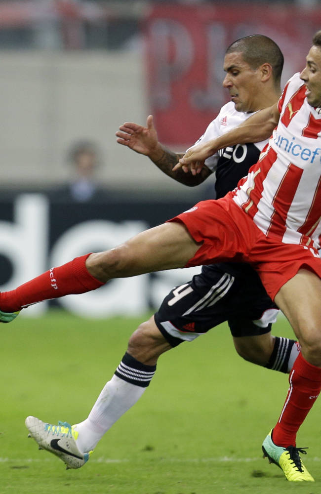 Olympiakos' David Fuster, right, and Benfica's Ezequiel Garay fight for the ball during their Champions League group C soccer match at the Karaiskaki stadium, in the port of Piraeus, near Athens, Tuesday, Nov. 5, 2013