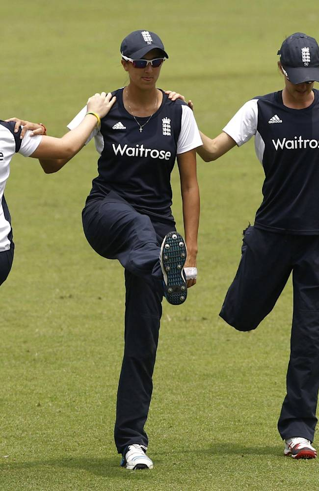 England women's team cricket players perform stretch exercises during a training session ahead of their ICC Twenty20 Cricket World Cup final match against Australia in Dhaka, Bangladesh, Saturday, April 5, 2014