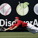 Los Angeles Angels' J.B. Shuck makes a diving catch on a ball hit by Cincinnati Reds' Neftali Soto during the second inning of an exhibition spring training baseball game Sunday, March 9, 2014, in Tempe, Ariz The Associated Press