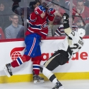 Montreal Canadiens defenceman Alexei Emelin, left, collides with Pittsburgh Penguins right winger Craig Adams during first-period NHL hockey game action in Montreal, Saturday, Nov. 23, 2013 The Associated Press