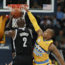 Brooklyn Nets forward Kevin Garnett, left, goes up for a shot as Denver Nuggets guard Randy Foye covers in the third quarter of the Nets' 112-89 victory in an NBA basketball game in Denver on Thursday, Feb. 27, 2014 The Associated Press