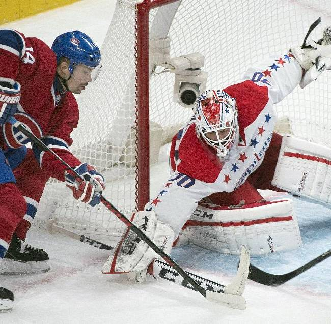 Washington Capitals goaltender Braden Holtby, right, makes a save against Montreal Canadiens' Tomas Plekanec during the third period of an NHL hockey game in Montreal, Saturday, Jan. 25, 2014