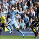 Manchester City's David Silva, left, shoots past Tottenham's Younes Kaboul during the English Premier soccer match between Manchester City and Tottenham Hotspur at the Etihad Stadium, Manchester, England, Saturday Oct. 18, 2014
