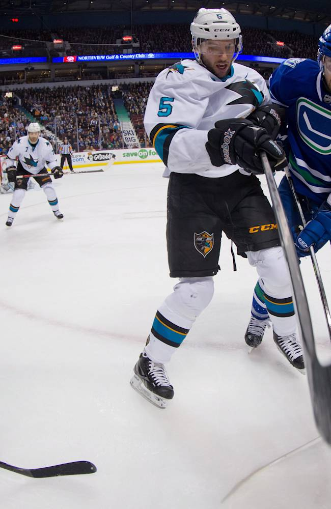 San Jose Sharks' Jason Demers, center, and Vancouver Canucks' Brad Richardson vie for the puck as Sharks' Matt Nieto, left, and Joe Pavelski, right, watch during the first period of an NHL hockey game, Thursday, Nov. 14, 2013 in Vancouver, British Columbia